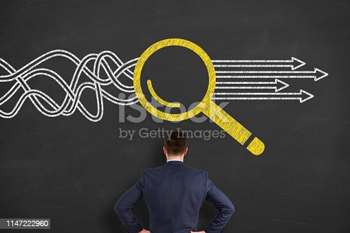 istock Solution Concept with Magnifying Glass on Chalkboard Background 1147222960