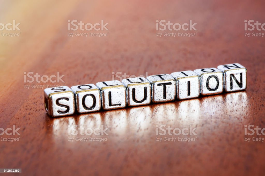 solution letters placed on a desk in precious wood stock photo