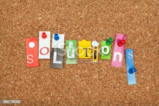 ' Solutions ' colorful single letters pinned on cork noticeboard