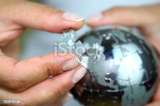 istock Solving globe puzzle 182876136
