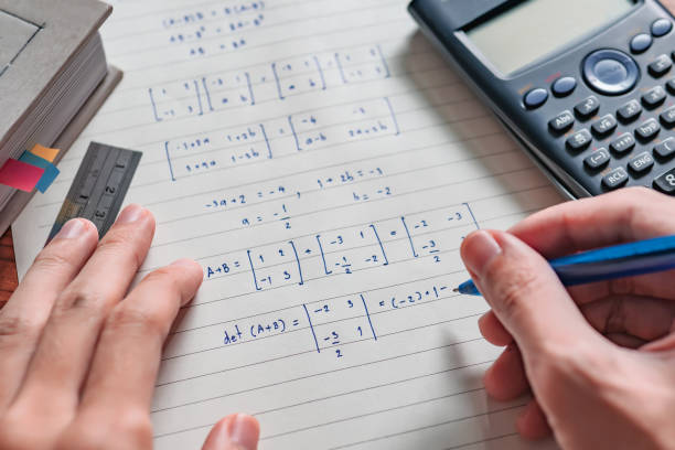 Solving math problem on paper stock photo