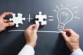istock Solving puzzle together. Drawing light bulb on blackboard. 543081654