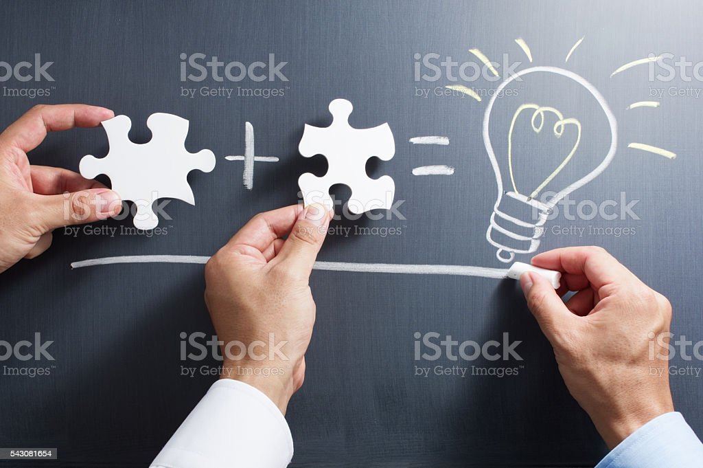 Solving puzzle together. Drawing light bulb on blackboard. stock photo