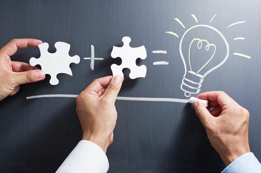 Solving Puzzle Together Drawing Light Bulb On Blackboard Foto de stock y más banco de imágenes de Adulto