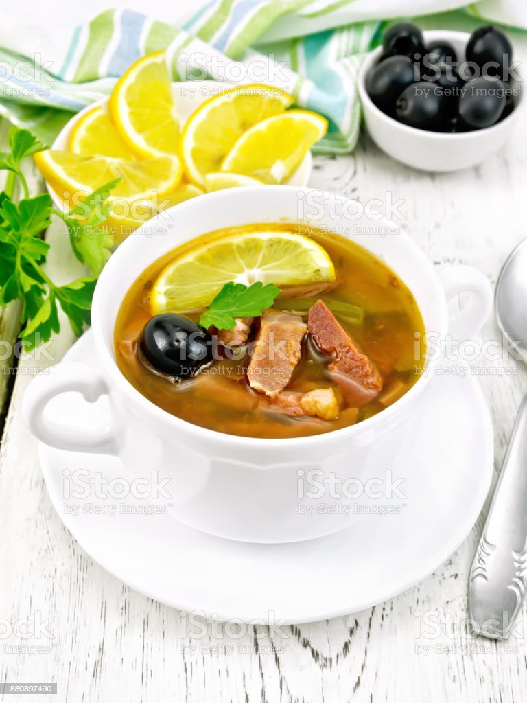 Solyanka with black olives in white bowl on board stock photo