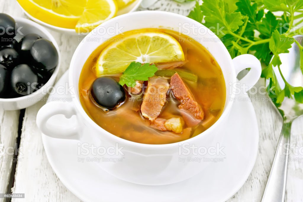 Solyanka with lemon in white bowl on board stock photo
