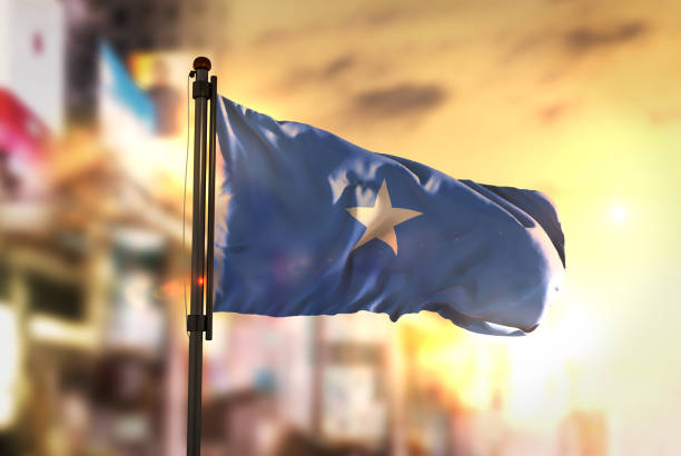 somalia flag against city blurred background at sunrise backlight - somalia stock photos and pictures