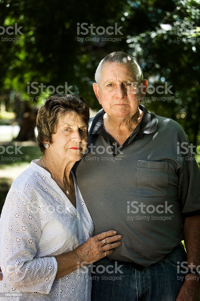 Somber looking elderly couple with trees in background royalty-free stock photo