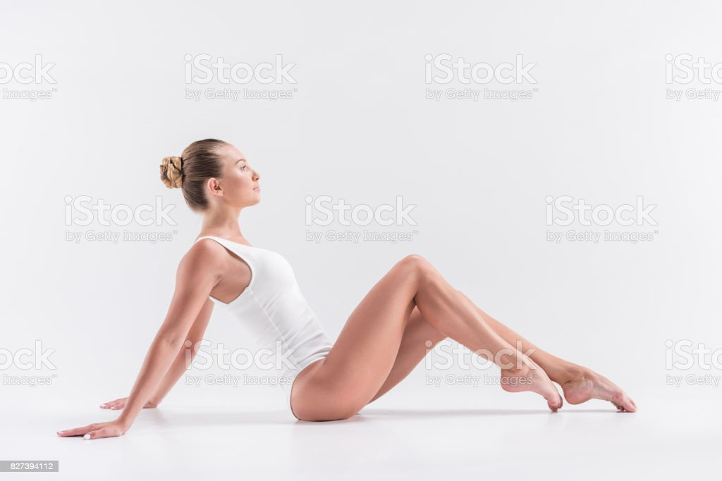Somber young lady gymnast recreating while exercising stock photo