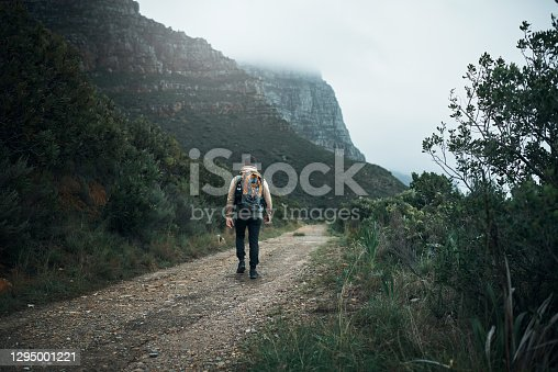 Rearview shot of a young man hiking through the mountains