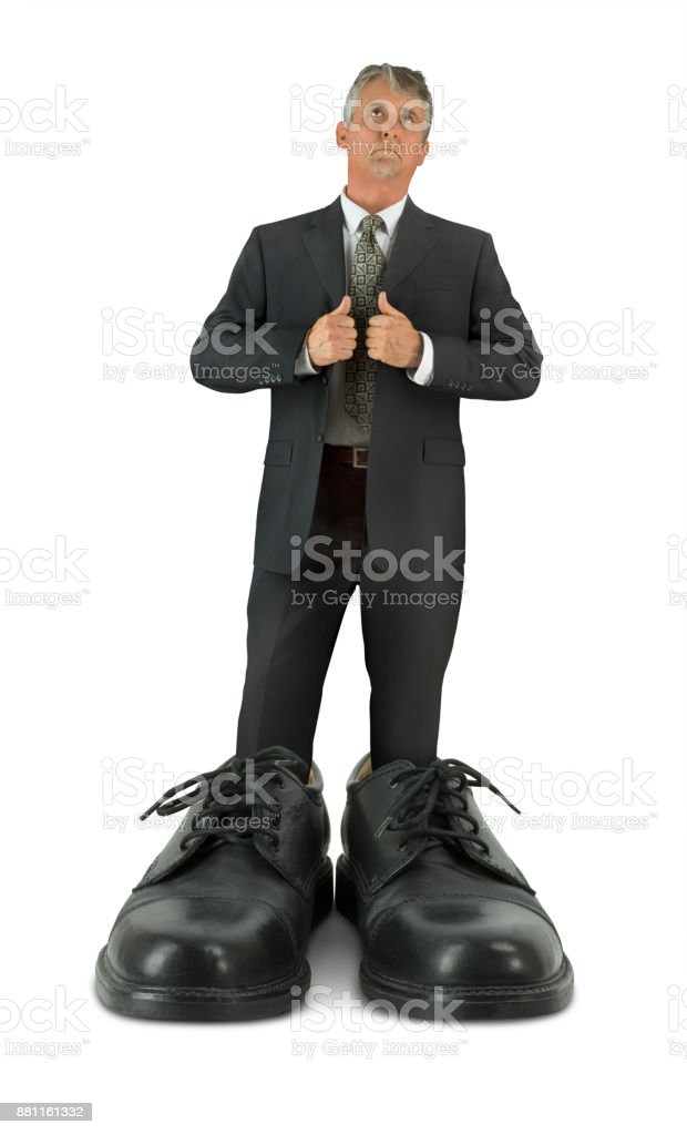 Some big shoes to fill man standing in giant shiny business footwear stock photo