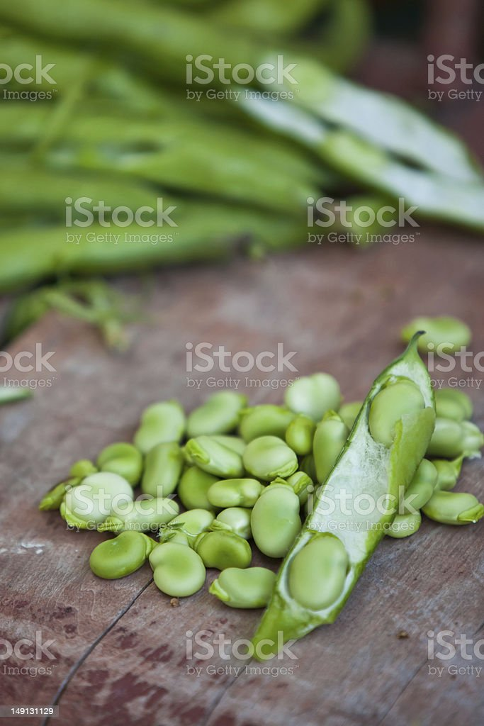 Some broad bean pods and beans on wooden surface royalty-free stock photo