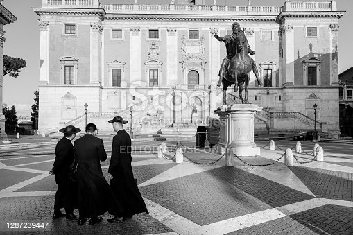 Rome, Italy, July 15 -- Some Catholic priests visit in solitude the Capitoline Hill square (Piazza del Campidoglio), taking photos and selfies. At right the bronze copy of the majestic equestrian statue of Emperor Marcus Aurelius. The original statue of Marcus Aurelius is kept inside the Capitoline Museums. The square was designed by Michelangelo Buonarroti and currently the Campidoglio is the seat of the Municipality of Rome. Image in High Definition format