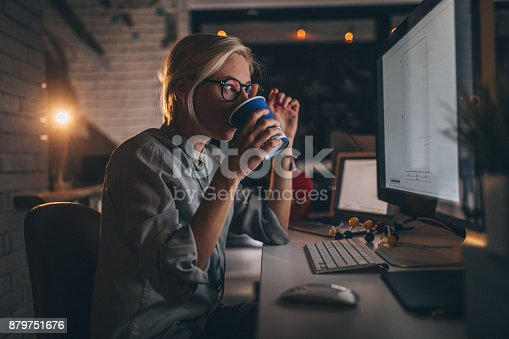 Photo of a young woman sitting at her desktop computer, having some hot coffee to help her trough a late night shift