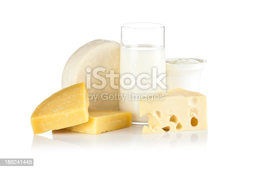 Dairy Products against white background. A glass of milk is in the center and a various types of cheese are around it. Beside the glass is a cup of yogurt. Visible reflection on foreground. Predominant colors are white and yellow. DSRL studio shot with Canon EOS 5D Mk II