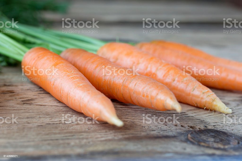 Some fresh carrots on old wooden desk stock photo