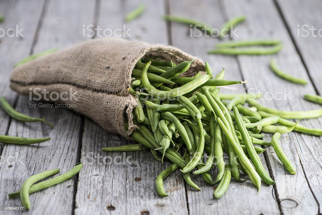 Some Green Beans on wood stock photo