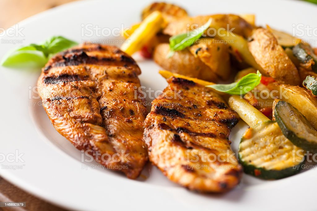 Some grilled chicken breast and vegetables  stock photo