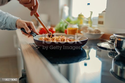 Cropped Image of Woman Cooking Pasta, Making Sauce Using a Pan at Home in the Kitchen. Unrecognizable Middle Aged Woman Making Lunch in Her Kitchen. Food, Eating, Culinary and People Concept
