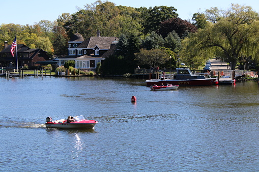 Some houses and a boat dock in the beautiful little town of Saugatuck in Michigan, USA. Some boats are out on the water including some speedboats and a Fire/Rescue boat with STFD