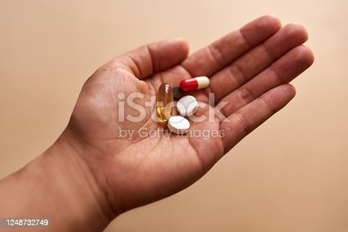 Studio shot of an unrecognisable woman holding a handful of pills against a brown background