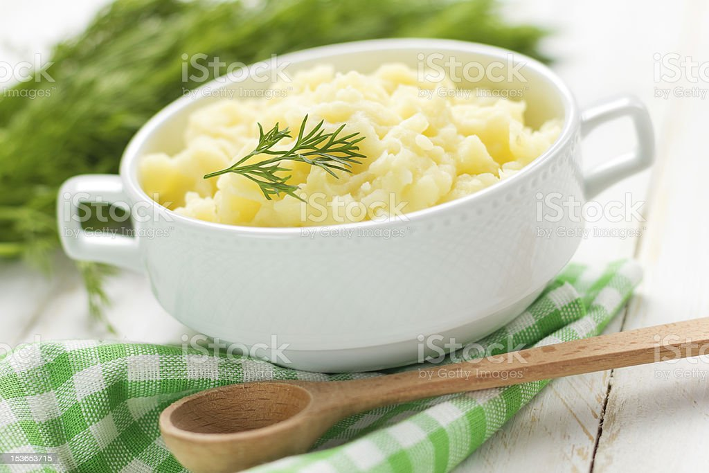 Some mashed potatoes with a wooden spoon and green napkin  stock photo