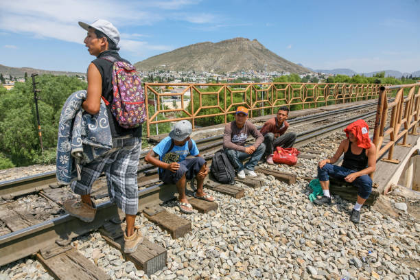 "Some migrants along the train line to the border between Mexico and the United States Coahuila, Mexico, Jun 16 - A group of migrants of Central American origin waits on the railway line to get on a container train, known as ""The Beast"", to reach the border line between the United States and Mexico. frontier field stock pictures, royalty-free photos & images"