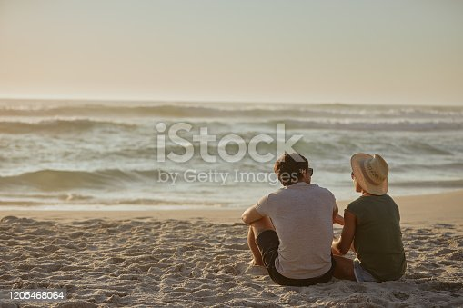 Rearview shot of a happy young couple relaxing together on the beach at sunset