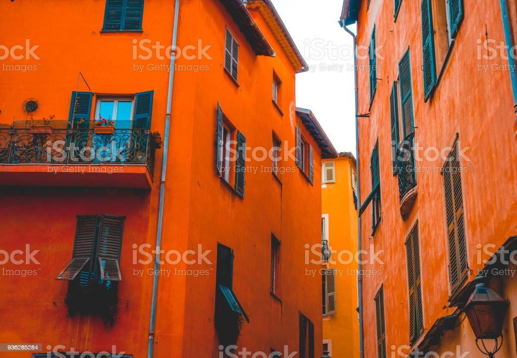 some orange buildings in a alley at nice stock photo