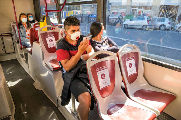 Some passengers with medical mask inside a public bus in Rome maintain social distancing stock photo