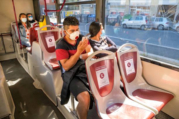 Certains passagers avec un masque médical à l'intérieur d'un bus public à Rome maintiennent la distanciation sociale - Photo