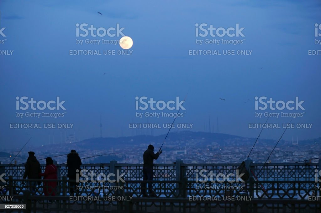 Some people are fishing and others are walking on The Galata Bridge at Istanbul with moon - Royalty-free Beauty Stock Photo