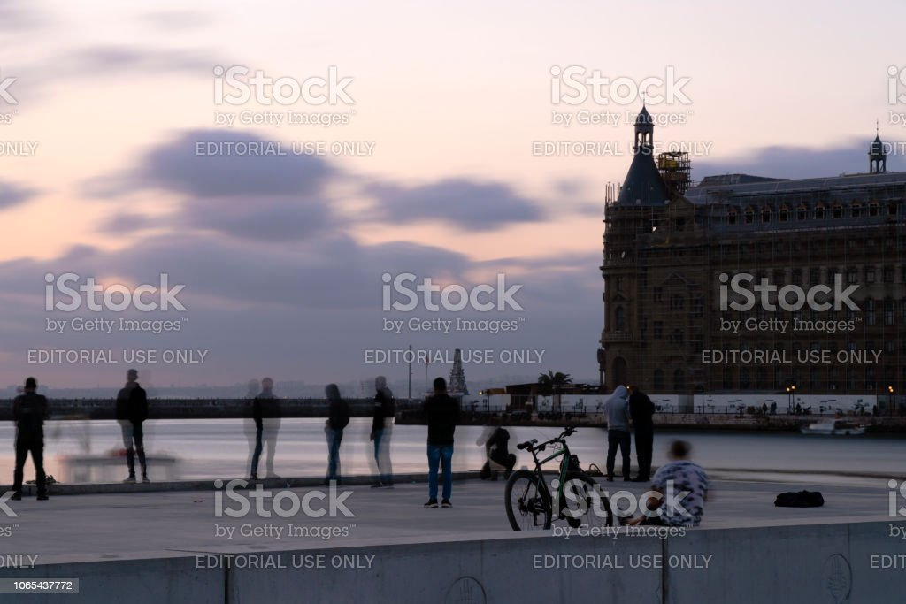 Some people are taking photo near the sea at The Kadikoy at sunset time stock photo
