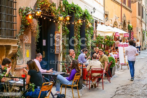 Rome, Italy, May 22 -- Some persons sitting outside a bar enjoy an aperitif in Trastevere in Rome during the slow reopening to a normal life after the lockdown due to the Covid-19. Image in HD format.