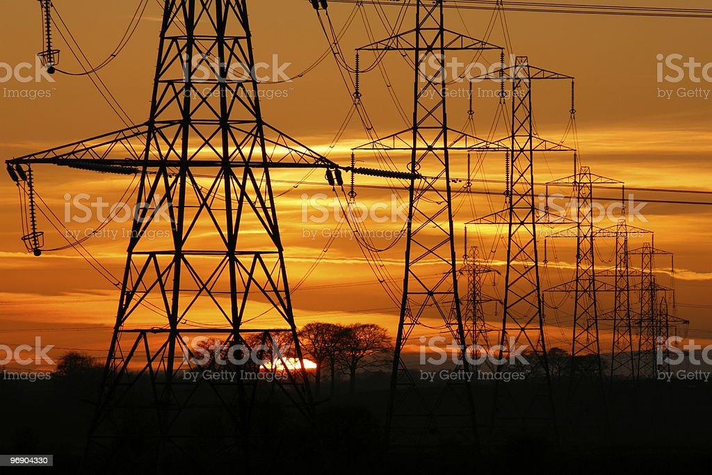 Some pylon power in the desert when the sun is setting royalty-free stock photo