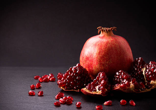 Some red pomegranates on black slate plate Some red juicy pomegranate, whole and broken, on black slate plate armenian culture stock pictures, royalty-free photos & images