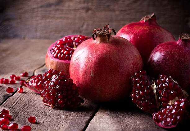 some red pomegranates on old wooden table - pomegranate stock photos and pictures