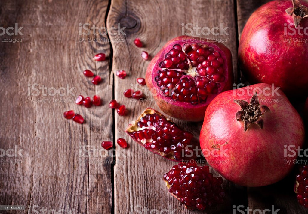 Some red pomegranates on old wooden table - Royalty-free 2015 Stock Photo
