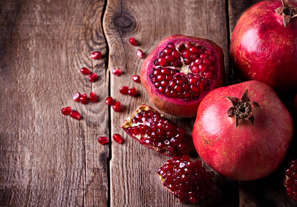 Some red pomegranates on old wooden table stock photo