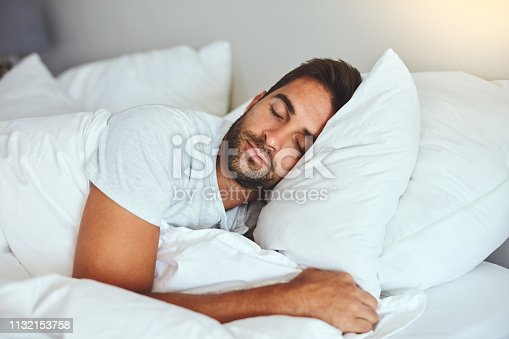 Cropped shot of a handsome young man sleeping comfortably in his bed at home