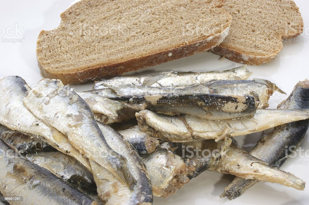 some sprats and bread on a white plate royalty-free stock photo