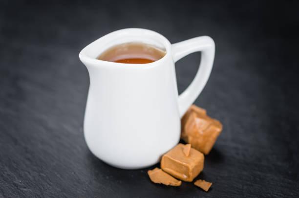 einige sirup (karamellgeschmack) auf einer dunklen schiefer tafel - karamellsirup stock-fotos und bilder