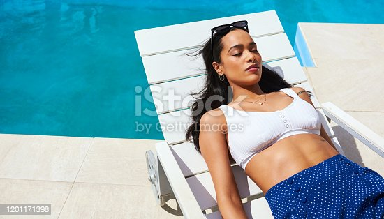 Cropped shot of a beautiful young woman relaxing on a lounger by the poolside