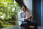A Japanese businessman working on a project using digital tablet and looking outside the window