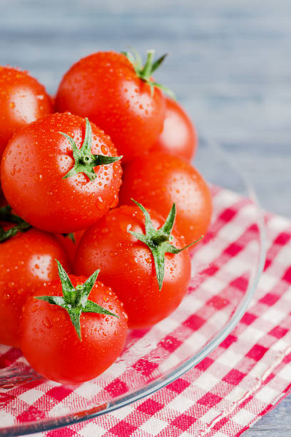 Some tomatoes on trasparent dish on wooden blue background - foto stock