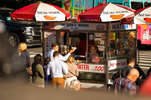 einige touristen sind hotdogs von einem kiosk auf dem times square kaufen. - mittagspause schild stock-fotos und bilder