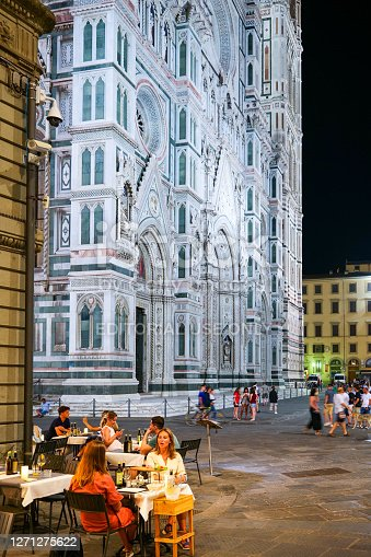 Florence, Italy, August 11 - Some tourists enjoy a dinner in the Piazza del Duomo of Santa Maria del Fiore in Florence. The Duomo is the third Cathedral in Europe, after St. Peter's in Rome and St. Paul's in London. The construction work began in 1296, while the consecration of the temple took place in 1436. The pedestrian area near the Duomo is much loved by residents and tourists for the beauty of the buildings and monuments and for the presence of many restaurants serving Italian cuisine. Image in High Definition format.