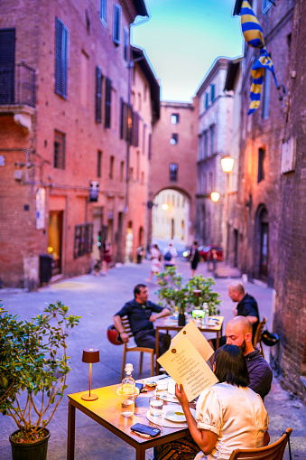 Siena, Tuscany, Italy, July 07 -- Some tourists enjoy life in a typical Italian restaurant along a lovely alley in the historic and artistic heart of the medieval city of Siena, in central Italy. Siena is one of the most famous Italian cities of art, in the heart of the Tuscan hills, famous for its immense artistic and historical heritage and for the Palio, where the seventeen districts of the city compete each year in one of the oldest horse races. of the world. Since 1995 the historic center of Siena has been a UNESCO World Heritage Site. Image in High Definition format.
