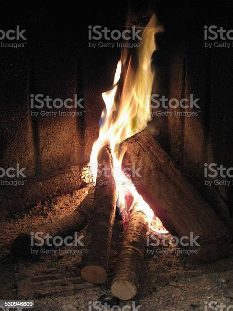 Photo of Some trunks of wood burn on red, yellow flame, fire