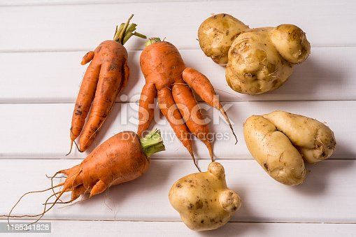 Flat lay Some ugly curved ogranic carrots and potatoes on white wooden background.